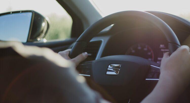 Un homme prend le volant avec les deux mains pour bien conduire en été.